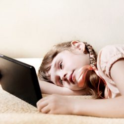 47757510 – tired little girl with tablet computer on the couch